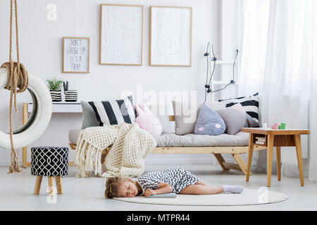 Robe fille Cute dans lying on floor in modern scandi prix Banque D'Images