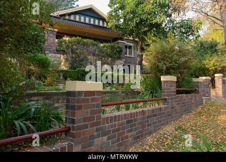 Un toit en tuiles, 1928, façade en brique double gable, Californie Accueil Bungalow avec une clôture avant de brique sur la rive nord de Sydney en Nouvelle-Galles du Sud en Australie Banque D'Images