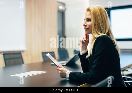 Attractive businesswoman using digital tablet in office Banque D'Images