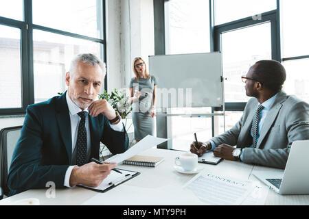 Senior businessman looking at camera while having conversation avec des collègues de l'assemblée d'affaires Banque D'Images