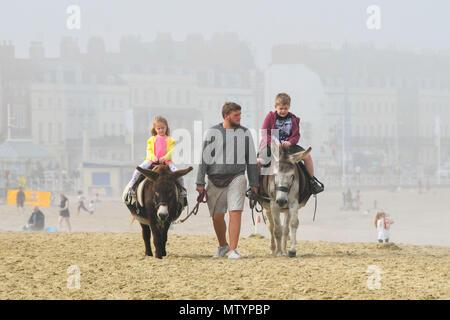 Weymouth, Dorset, UK. 31 mai 2018. Météo britannique. Les enfants bénéficiant d'un tour de l'âne à la plage en fin d'après-midi à la station balnéaire de Weymouth, dans le Dorset comme le brouillard de mer épaissit après une bande d'averses avaient déjà franchi. Crédit photo: Graham Hunt/Alamy Live News Banque D'Images