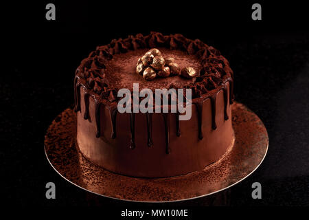 Gâteau au chocolat avec des noix sur fond noir Banque D'Images