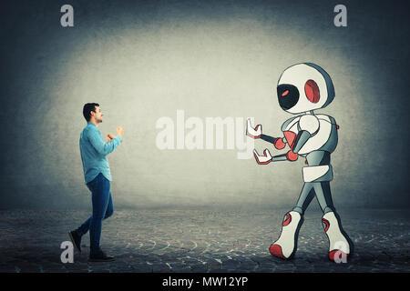 Young businessman holding poings prêts à lutter contre le robot. La rivalité entre l'humain et la technologie. Danger de perdre l'emploi, le remplacement du travail humain Banque D'Images