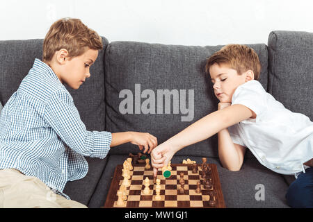 Cute little boys playing chess while sitting on sofa at home Banque D'Images