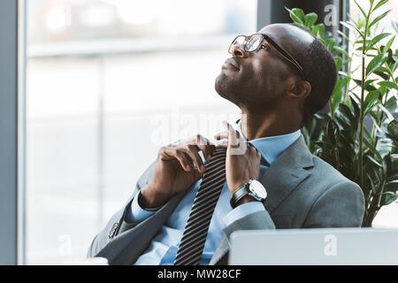 Young african american businessman adjusting necktie lunettes dans et à l'écart dans office Banque D'Images