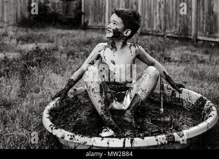 Jeune garçon ayant du plaisir à jouer dans la boue. Banque D'Images