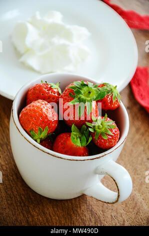 Les fraises mûres fraîches entières dans une tasse à café de crème fouettée. Close up, table en bois. Banque D'Images