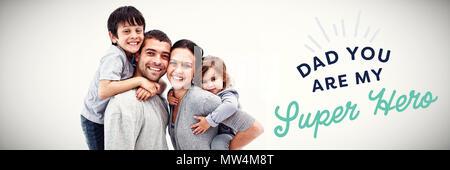 Les parents de donner aux enfants piggyback rides Banque D'Images