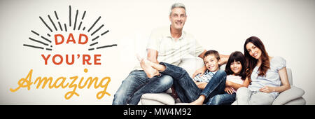 Image composite de family sitting on sofa smiling at camera Banque D'Images