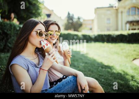 Deux jeunes femmes amis manger une glace assis sur l'herbe dans les rues de la ville Banque D'Images