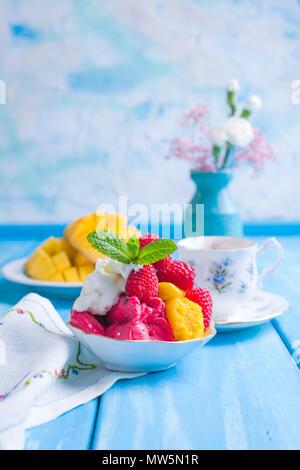 La crème glacée de fleurs aux couleurs vives avec des framboises et de la menthe dans une plaque, sur un fond en bois bleu. Une tasse de café le matin et de lumière et de fleurs. Vintage photo. Copy space Banque D'Images