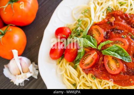Les pâtes Spaghetti aux tomates séchées, les tomates raisins, basilic et origan sauce, sur une table en bois noir. (Une série) Banque D'Images