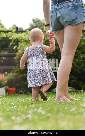 Belle Jeune fille bébé enfant à 18 mois avec des cheveux blonds courts walking in garden - modèle publié photographie prise par Simon Dack Banque D'Images
