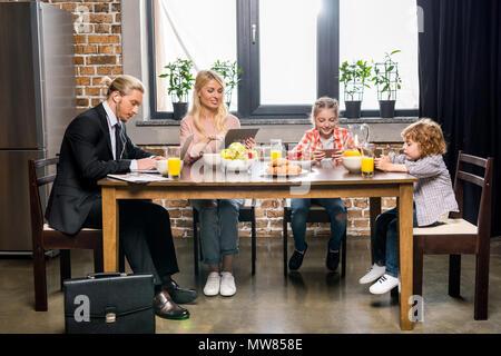 Jeune homme d'affaires avec la famille de prendre le petit déjeuner et l'utilisation d'appareils numériques à la maison Banque D'Images