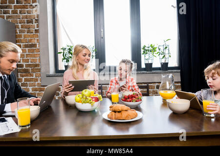 Jeune famille avec deux enfants à l'aide de périphériques numériques pendant le petit déjeuner Banque D'Images