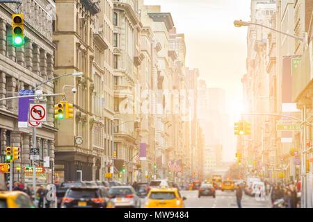 La lumière du soleil brille sur Broadway à New York City avec les gens et les voitures le long de la rue à travers Manhattan Banque D'Images