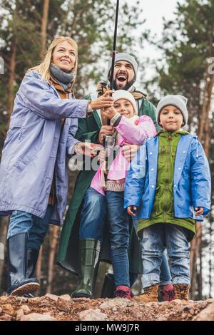 Heureux jeune famille dans d'imperméables de pêche ensemble Banque D'Images