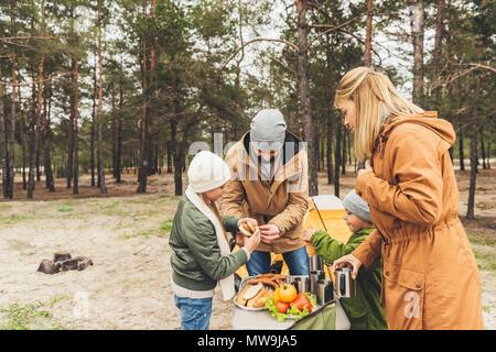 Happy Family having picnic sur la nature sur jour d'automne froid Banque D'Images