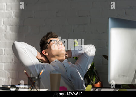 Beau jeune businessman relaxing at workplace in modern office Banque D'Images