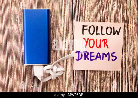 Suivez vos rêves motivational message manuscrit sur papier blanc au-dessus de l'arrière-plan en bois rétro. Concept avec une motivation positive mots sur la rétro arrière. Banque D'Images