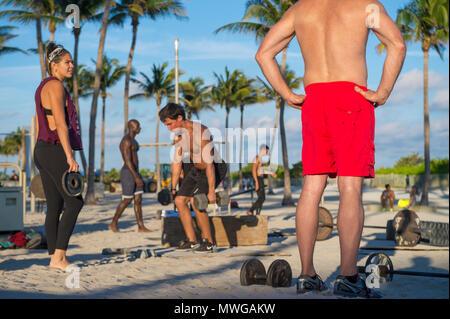 MIAMI - 29 décembre 2017: les jeunes hommes musclés s'entraîner dans la salle de sport en plein air appelé Muscle Beach dans le parc Lummus. Banque D'Images