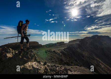 Sac à dos avec l'homme debout sur la roche près de Teide à Tenerife sur sun sur