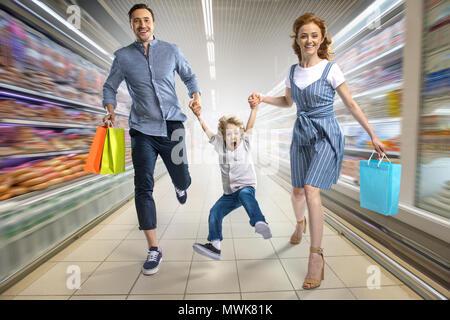 Les parents smiling with shopping bags tenant la main avec enthousiasme son in supermarket