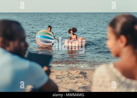 Cropped shot des parents assis sur la plage tandis que petits enfants jouant dans la mer Banque D'Images
