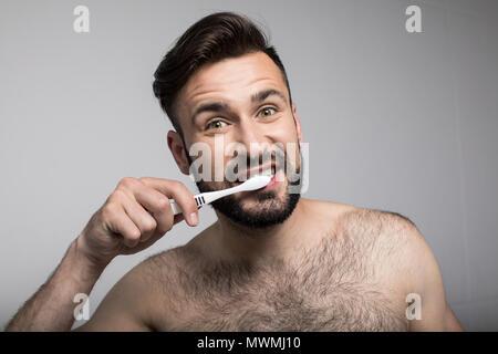 Beau jeune homme barbu se brosser les dents et à la caméra à l'isolé sur gray Banque D'Images