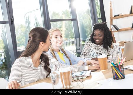 Portrait de société multiethnique cheerful businesswomen talking while sitting at au travail Banque D'Images