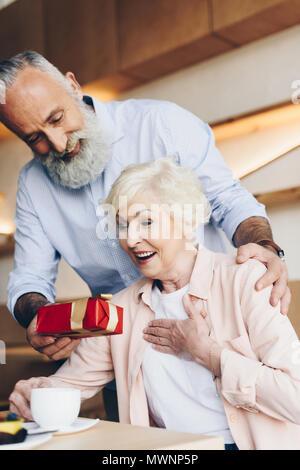 Senior man smiling surprenant épouse avec don en cafe Banque D'Images