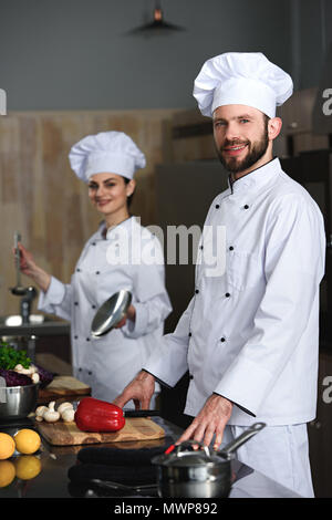 Les chefs professionnels man and woman cooking in restaurant kitchen Banque D'Images