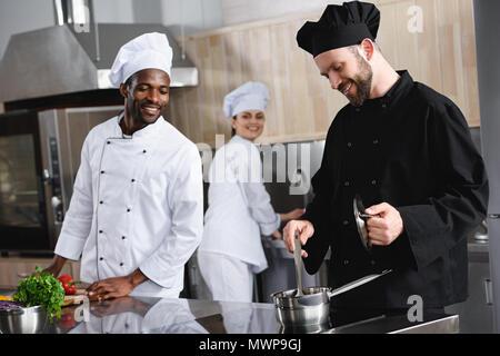 Smiling chefs cooking multiculturelle ensemble au restaurant de cuisine Banque D'Images