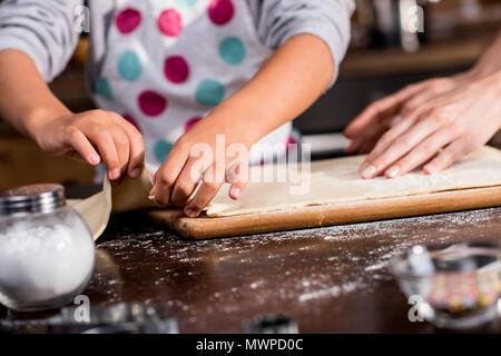 Cropped shot of family putting pâte crue sur une planche à découper pendant la cuisson ensemble Banque D'Images