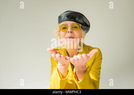 Woman élégant veste en cuir jaune et béret blowing kiss, isolé sur gray Banque D'Images