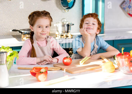 Adorables enfants en tabliers smiling at camera pendant la cuisson de légumes grillés together in kitchen Banque D'Images