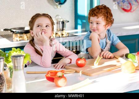 Mignon petit enfants dans la cuisine tabliers de cuisine ensemble dans une salade de légumes Banque D'Images