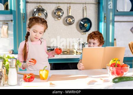 Les enfants avec les légumes et livre de cuisine dans la cuisine Banque D'Images
