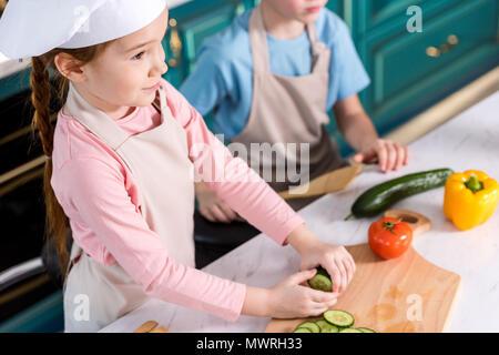 Cropped shot d'adorables petits enfants dans la cuisine tabliers de cuisine ensemble dans une salade de légumes Banque D'Images