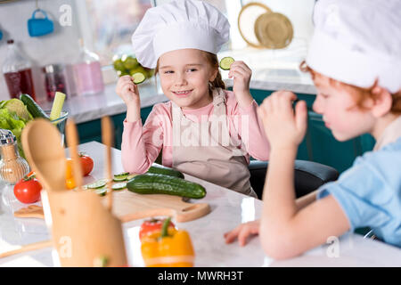 Cute little children en chef s'amuser ensemble pendant la cuisson dans la cuisine Banque D'Images
