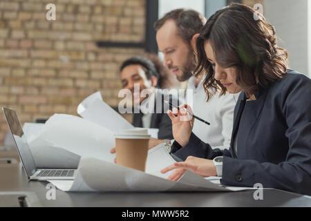 Équipe d'architectes travaillant sur les plans de l'immeuble à bureau moderne Banque D'Images