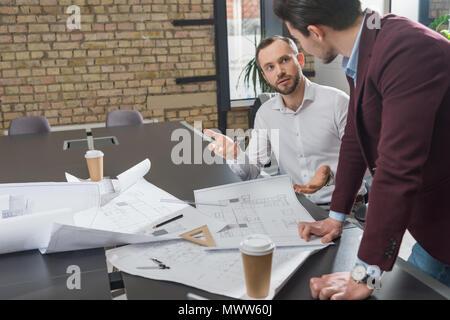 Architectes réussie sur les plans de construction de réflexion au bureau
