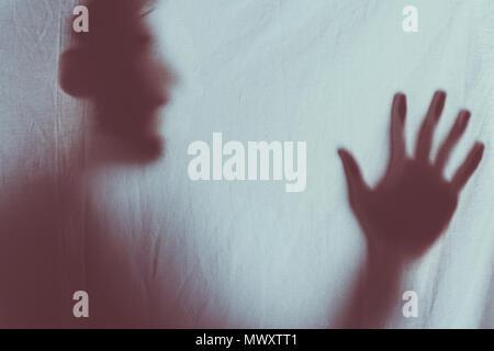 Silhouette floue effrayant de méconnaissable personne crier derrière voile Banque D'Images