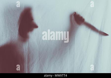 Silhouette floue effrayant de personne en criant et en tenant le couteau derrière voile Banque D'Images