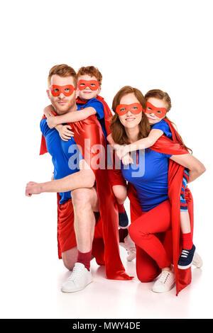 Super heureux parents usurpation de l'adorable smiling kids dans les masques et capes isolated on white Banque D'Images