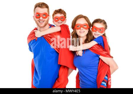 Les parents super usurpation enfants heureux dans les masques et capes isolated on white Banque D'Images