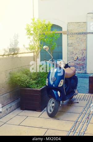 Scooter bleu sur une rue à côté d'une baignoire avec un peu d'arbre dans une journée ensoleillée.