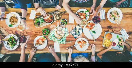 La consommation et les loisirs concept - groupe de personnes en train de dîner à table avec de la nourriture Banque D'Images
