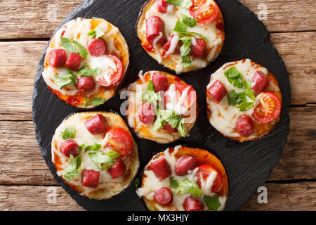 De l'aubergine cuite appétissante avec du fromage, des tomates, des saucisses et de l'herbe de close-up sur la table supérieure horizontale. Vue de dessus Banque D'Images