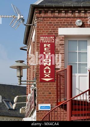 Panneau rouge sur le bâtiment en briques rouges avec la flèche pointant vers le bas: Produits Régionaux, ou des produits régionaux. Le Crotoy, France Banque D'Images